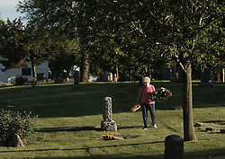 May 26, 2017 - Sioux City, IOWA, USA - VERLA HAACK, Sioux City, Iowa, places flowers next to grave markers in memory of her parents, husband and a daughter who succumbed to cancer for Memorial Day in Graceland Park Cemetery Friday, May 26, 2017. (Credit Image: © Jerry Mennenga via ZUMA Wire)