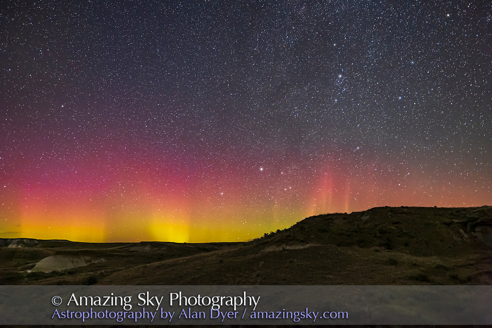 A dim red and green aurora from Dinosaur Provincial Park, Alberta, on August 29/30, 2021. There were expectations of a bigger display this night, but litte came to pass! Capella is rising at centre; Perseus is at top right.<br /> <br /> This is a stack of 4 exposures for the ground to smooth noise and one exposure for the sky, all 30 seconds at f/2.8 with the Canon 15-35mm RF lens at 25mm and the Canon R6 at ISO 4000.