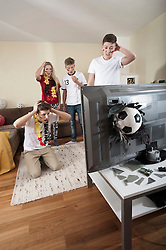 Teenage soccer fans in living room with ball demolishing TV