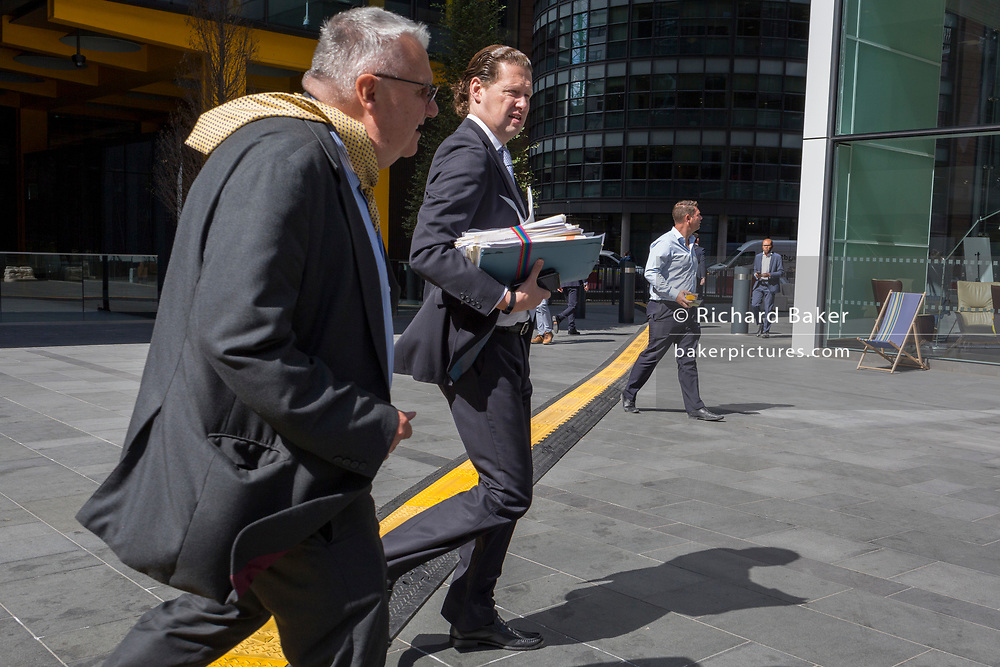 Business people cross a yellow line that covers hazardous electrical cabling at Leadenhall in the City of London, (aka The Square Mile) the capital's financial district, on 2nd September 2019, in London, England.