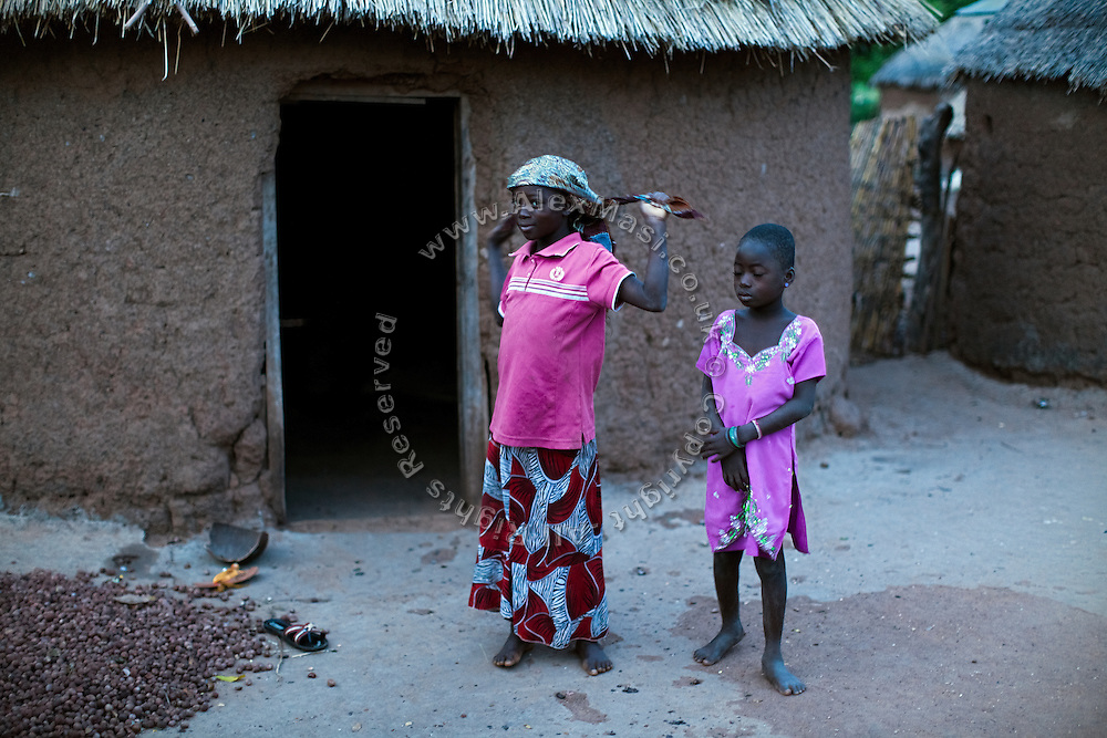 Before the sunrise, Hassana Ibrahim, 11, (left) is getting ready to leave her home and collect Shea nuts to help supporting her family, before returning to her village to attend school in Boggu, Tamale, northern Ghana.