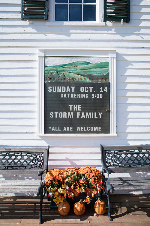 New England white clapboard Peru Congregational church notice board and Halloween pumpkins in Manchester, Vermont, USA