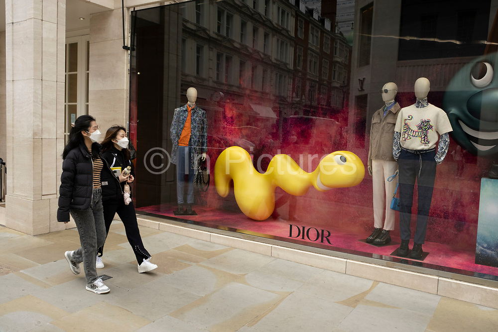 People pass the Dior store wearing face masks on Bond Street on 25th May 2021 in London, United Kingdom. These high end brands are seen next to each other on a very ordinary wall. Bond Street is one of the principal streets in the West End shopping district and is very upmarket. It has been a fashionable shopping street since the 18th century. The rich and wealthy shop here mostly for high end fashion and jewellery.