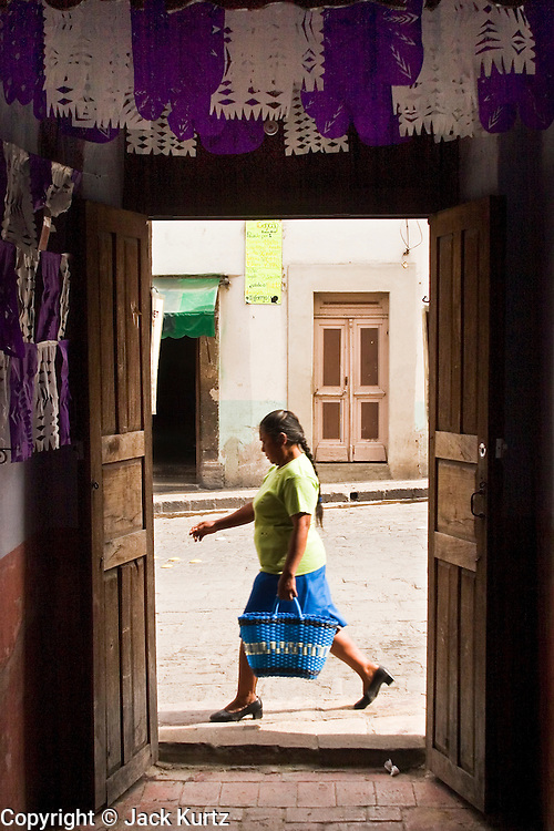 05 APRIL 2004 - SAN MIGUEL DE ALLENDE, GUANAJUATO, MEXICO: A woman walks past an open doorway in San Miguel de Allende. San Miguel, which was founded in the 1600s, is one of Mexico's premier colonial cities. It has very strict zoning and building codes meant to preserve the historic nature of the city center. About 7,500 US citizens, mostly retirees, live in San Miguel. PHOTO BY JACK KURTZ