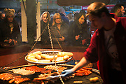 German bratwurst stall at the Christmas market doing a roaring trade as people queue for the grilled sausages. The South Bank is a significant arts and entertainment district, and home to an endless list of activities for Londoners, visitors and tourists alike.