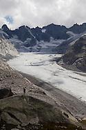 Un turista fotografa la testata della valle del forno con il suo ghiacciaio.
