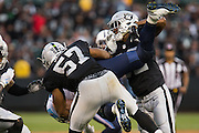 Oakland Raiders outside linebacker Cory James (57) and defensive back Antonio Hamilton (32) body slam Tennessee Titans wide receiver Harry Douglas (83) at Oakland Coliseum in Oakland, Calif., on August 26, 2016. (Stan Olszewski/Special to S.F. Examiner)