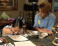 Directv Magazine -- Minda Cox (L) works on a painting as Camp Barnabas founder and director Cyndy Teas (R) watches Minda paint.
