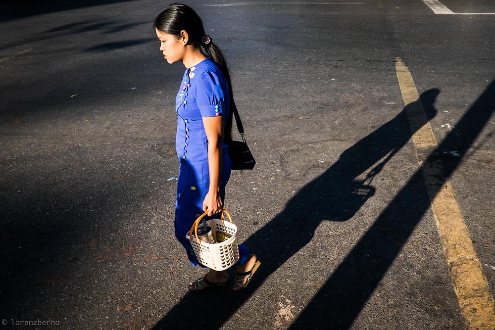 A burmese young woman is walking the street of Yangon, Myanmar. Photo by Lorenz Berna