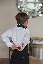 little boy at a wedding getting dressed