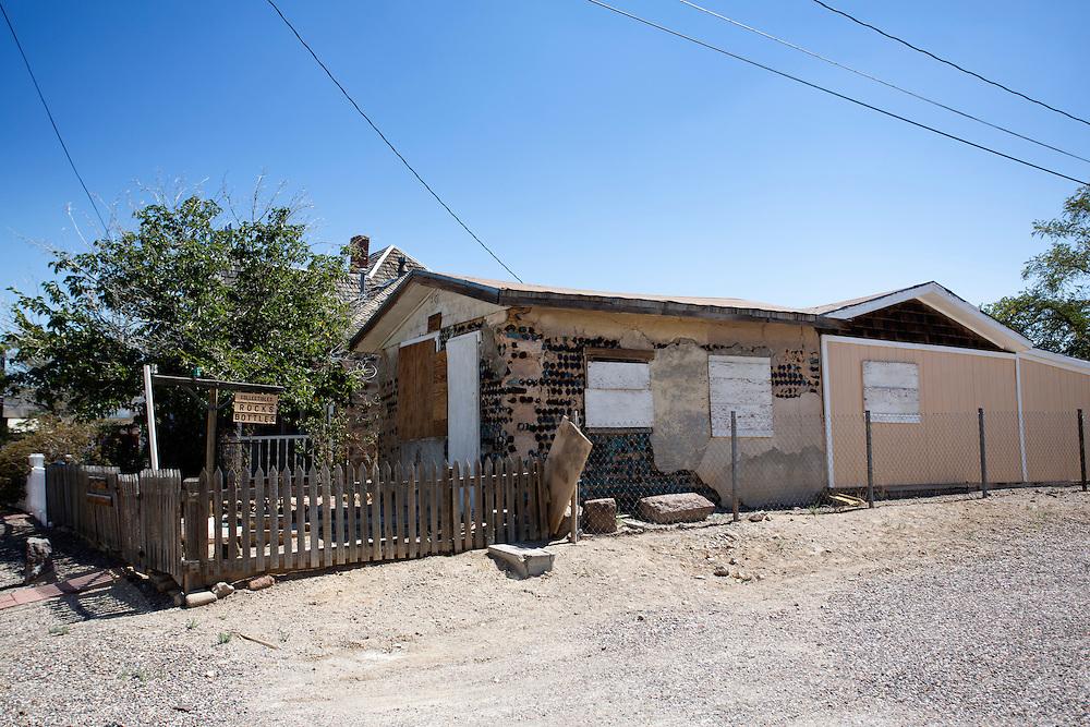 Het voormalig huis uit 1905 van mijnbouwkundig ingenieur E.A. Byler gemaakt met flessen. Goldfield, Nevada, is een bijna verlaten ghost town in Esmeralda County, gelegen aan de State Route 95. Tussen 1906 en 1910 was Goldfield de grootste plaats in de Amerikaanse staat Nevada met meer dan 20.000 inwoners. Momenteel leven er tussen de 200 en 300 mensen. Het plaatsje is groot geworden door de vondst van goud in 1902. Vanaf 1910 daalde het aantal inwoners snel en in 1923 is een groot deel verwoest door een brand. De overgebleven huizen zijn grotendeels verlaten, maar worden nog altijd onderhouden door de inwoners. Daarmee wordt de geschiedenis van de het plaatsje bewaard.<br /> <br /> The bottle house of mining engineer E.A. Byler of 1905. Goldfield, Nevada, is an almost deserted ghost town in Esmeralda County. Between 1906 and 1910, Goldfield was the largest town in the state of Nevada with more than 20,000 inhabitants. Currently, there are between 200 and 300 people. The town has grown with the discovery of gold in 1902. From 1910, the population declined rapidly, and in 1923 the town was largely destroyed by a fire. The remaining houses are largely abandoned, but are still maintained by the residents. This way the history of the town is preserved.