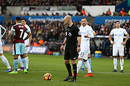 referee Anthony Taylor places the ball on the penalty spot after Sam Vokes of Burnley handles the ball in the area but the referee Anthony Taylor thinks it was a Swansea city players arm and awards the penalty to Burnley by mistake. Burnley's Andre Gray goes on to score the penalty. Premier league match, Swansea city v Burnley at the Liberty Stadium in Swansea, South Wales on Saturday 4th March 2017.<br /> pic by Andrew Orchard, Andrew Orchard sports photography.