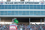 Texas Gov. Rick Perry practices waving the green flag before the start of the Sprint Cup NRA 500 at Texas Motor Speedway in Fort Worth on Saturday, April 13, 2013. (Cooper Neill/The Dallas Morning News)