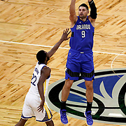 ORLANDO, FL - FEBRUARY 19:  Nikola Vucevic #9 of the Orlando Magic attempts a shot over Andrew Wiggins #22 of the Golden State Warriors during the first half at Amway Center on February 19, 2021 in Orlando, Florida. NOTE TO USER: User expressly acknowledges and agrees that, by downloading and or using this photograph, User is consenting to the terms and conditions of the Getty Images License Agreement. (Photo by Alex Menendez/Getty Images)*** Local Caption *** Nikola Vucevic; Andrew Wiggins