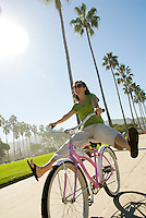 A young woman rides a cruiser bike in southern California.