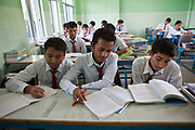 Male Nepalese pupils studying in a classroom in the Rara Hill Memorial School run by the community in the Kiretipur area of Kathmandu Valley, Nepal.  The boys are reading and writing in their exercise books next to a large pile of education books. They all wear school uniform.