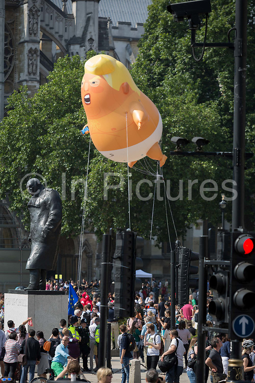 The inflatable balloon called Baby Trump flies above the statue of wartime Brish Prime Minister Winston Churchill in Parliament Square, Westminster, the seat of the UK Parliament, during the US Presidents visit to the UK, on 13th July 2018, in London, England. Baby Trump is a 20ft high orange blimp depicting the US President as an enraged, smartphone-clutching infant - and given special permission to appear above the capital by London Mayor Sadiq Khan because of its protest rather than artistic nature. It is the brainchild of Graphic designer Matt Bonner.