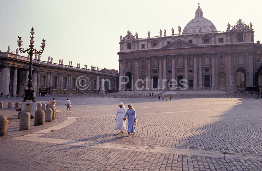 Two nuns with their early morning shadows, walk over the cobbles of St. Peters Square in front of the Vatican, on 3rd November 1999, in Rome, Italy.