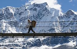 THEMENBILD - Trekkingtour in Nepal um die Annapurna Gebirgskette im Himalaya Gebirge. Das Bild wurde im Zuge einer 210 Kilometer langen Wanderung im Annapurna Gebiet zwischen 01. September 2012 und 15. September 2012 aufgenommen. im Bild ein Träger auf einer Hängebrücke vor der Chulu Südwand, in der Bildmitte der 6250 m hohe Chulu Central Peak // THEME IMAGE FEATURE - Trekking in Nepal around Annapurna massif at himalaya mountain range. The image was taken between september 1. 2012 and september 15. 2012. Picture shows Porter on swing bridge in front of southface of chulu, in the middle of the image is the 6250 m high Chulu Central Peak, NEP, EXPA Pictures © 2012, PhotoCredit: EXPA/ M. Gruber