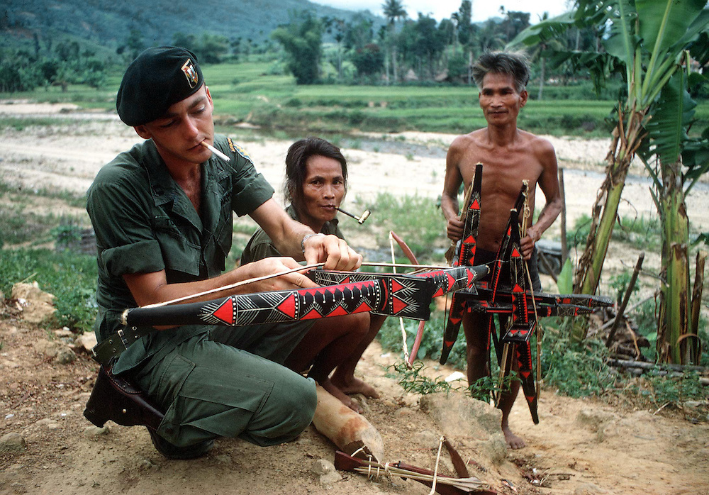 A soldier of the American Special Forces is seen making friends with the Montanards in the Central Highlands of Vietnam during the war. October 1970. Photographed by Terry Fincher