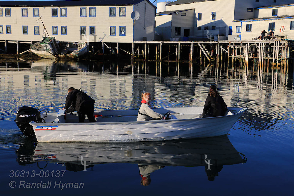 Kirsten Wollan pilots motorboat from harbor with her only student, Andrine Klausen, and mother to fish cod for dinner in the town of Ingoy on Ingoya island, Finnmark, Norway.