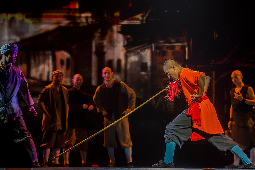 """A monk bends a spear while pushing the point against his neck - Twenty Shaolin monks, from their  temple in the foothills of the Song Shang mountain range in China's Henan province, take to the stage to demonstrate their martial arts expertise in an 'awe-inspiring' performance. SHAOLIN is a display of theatre and physical prowess in which the cast perform """"superhuman"""" feats. The show combines traditional Shaolin Kung Fu, inch perfect choreography with dramatic lighting and sound that evokes the spirit of their tradition – their Temple being the birthplace of Kung Fu.  These are the very best Shaolin Kung Fu experts on the planet and they have come together to create this show. The Shaolin Monks are lifted aloft on sharpened spears, break marble slabs with their heads, perform handstands on two finger tips,splinter wooden staves with their bodies, break bricks on their heads and fly through the air in a series of incredible back flips. The show embarks upon a three-week run at The Peacock Theatre, London from 29 September – 17 October 2015."""