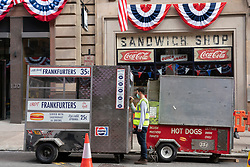 Glasgow, Scotland, UK. 10 July  2021. Workers transforming the centre of Glasgow city centre into a replica of downtown New York City for the new Indiana Jones movie that will be filmed in Glasgow this month. Set decorations include the creation of authentic New York cafes and businesses and the erection of many Stars and Stripes flags. Pic; Sign-writer paints lettering onto hot dog stall. Iain Masterton/Alamy Live news.