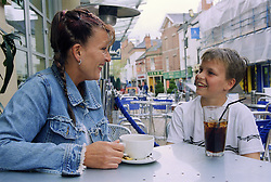 Single mother sitting at table outside cafe with young son smiling,