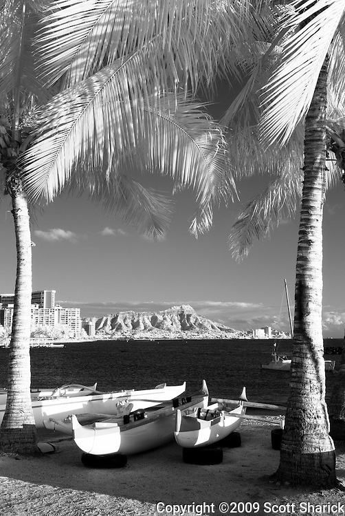An infrared image with outrigger canoes in the foreground and Diamond Head in the background.