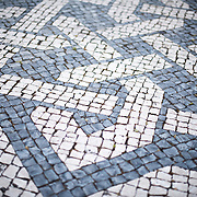 LISBON, Portugal - Black and white mosaic tiles lining Rossio Square. Formally known as Pedro IV Square (or Praça de D. Pedro IV in Portuguese), Rossio Square has been a vibrant public commons in Lisbon for centuries. At its center stands a column topped with a statue of King Pedro IV (Peter IV; 1798-1834) that was erected in 1870.