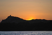 View from Sanary over the sea towards St Pierre des Embiez island at sunset, sun disappearing behind the island, dark sea and sky bright yellow orange Le Brusc Six Fours Var Cote d'Azur France