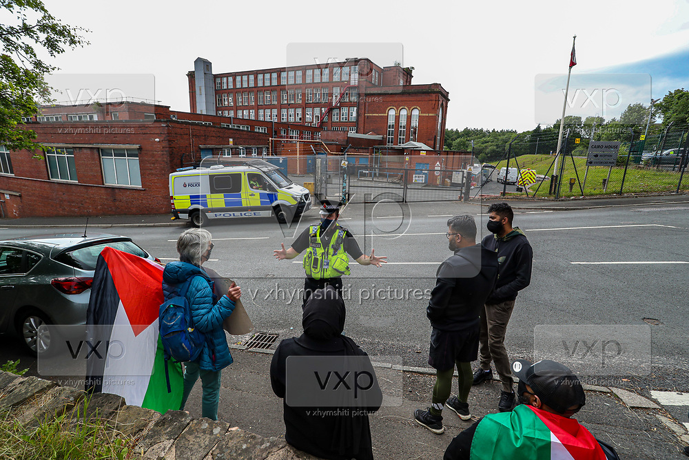 """Oldham, United Kingdom, June 21, 2021: A policeman talks to the people wearing face protective masks who are gathered outside """"Cairo House"""" in Oldham on Monday, June 21, 2021 - following the arrest of Palestine Action activists after they scaled the roof Monday morning. This is the ongoing protest forms of the human rights activists group in Britain targeting an Israeli owned weapons manufacturer Elbit Systems. Activists argue that arms being manufactured in the facility are being used in indiscriminate attacks against the Gaza Strip. (VX Photo/ Vudi Xhymshiti)"""