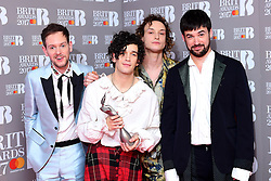 The 1975's Adam Hann (L - R), George Daniel, Ross MacDonald and Matthew Healy with the Best British Group Award in the press room during the Brit Awards at the O2 Arena, London.