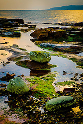 Evening light on the rocks at Little Skate Bay on the west coast of the island of Great Cumbrae, Scotland.  The Isle of Bute can be seen in the background.<br /> <br /> (c) Andrew Wilson   Edinburgh Elite media