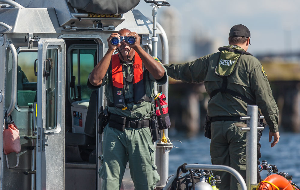 A King County Sheriff's deputy takes a closer look at protesters blocking the entrance of the Polar Pioneer oil rig docking in Elliott Bay Tuesday, May 26, to pick up supplies before heading to the Arctic Ocean to drill for oil. © N. Scott Trimble