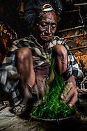A Naga Tribesman prepares opium