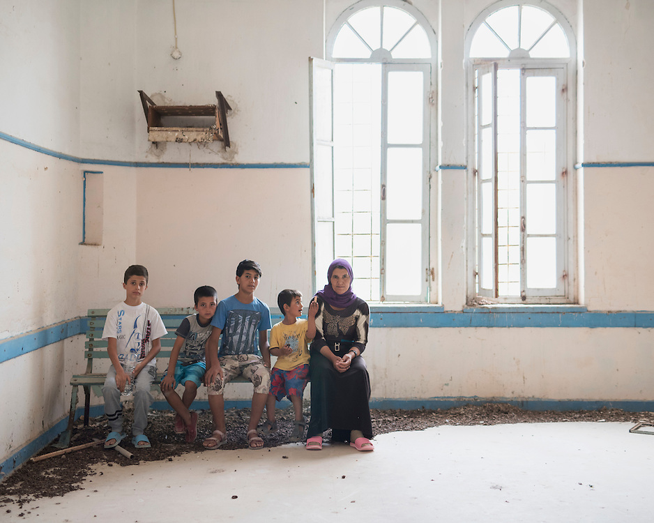 Refugees Diar, 13, Rebas, 9, Youssef, 14, Naswan, 5, and Kosh, 48, sitting in a room in the abandoned Lepida psychiatric hospital in whose grounds the Leros 'Hot spot' (an EU-run migrant's reception centre)  has been built. <br /> <br /> Originally constructed, in 1930 by fascist Italy, as barracks for Italian soldiers serving in the aeronautical base of Portolago, it was then, for a short period after WWII, a re-education camp for the children of Greek Communists. In 1958, it was converted into the biggest psychiatric hospital in the country. The conditions for the patients were horrific and it was shut down in the late 1980s and the patients moved into smaller buildings in the grounds and elsewhere on the island.