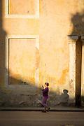 Woman walking on street using her smart phone, Havana, Cuba