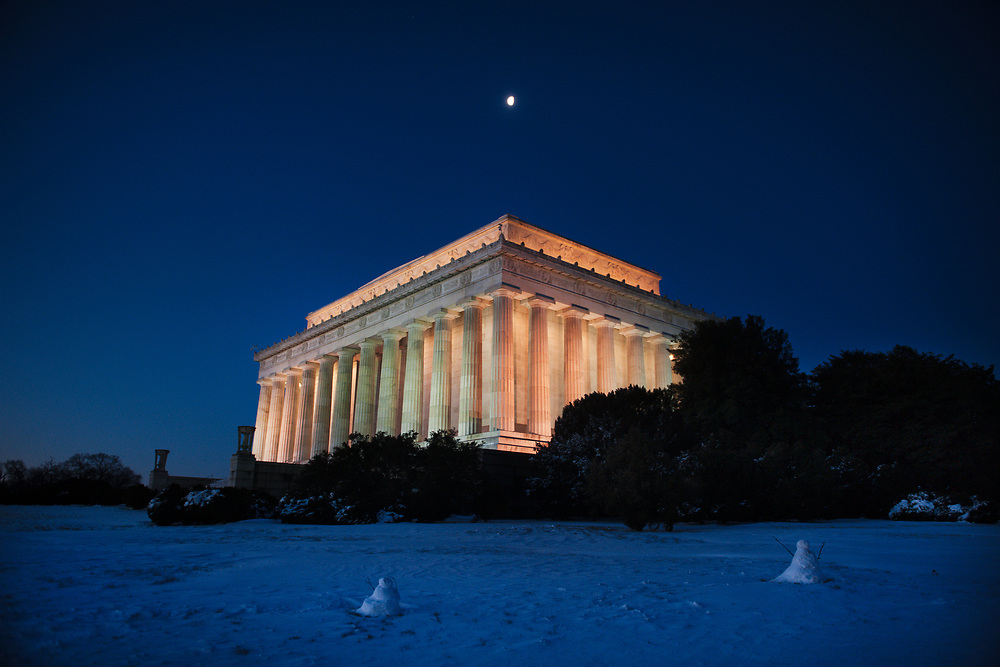 A wintery scene surrounds the Lincoln Memorial under a crescent moon in the early morning. Washington, D.C.