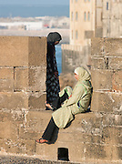 Young girls sit at the ramparts on the fortified sea wall at the medina in Essaouira, Morocco