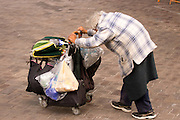 A homeless person pushing their cart with their possessions.