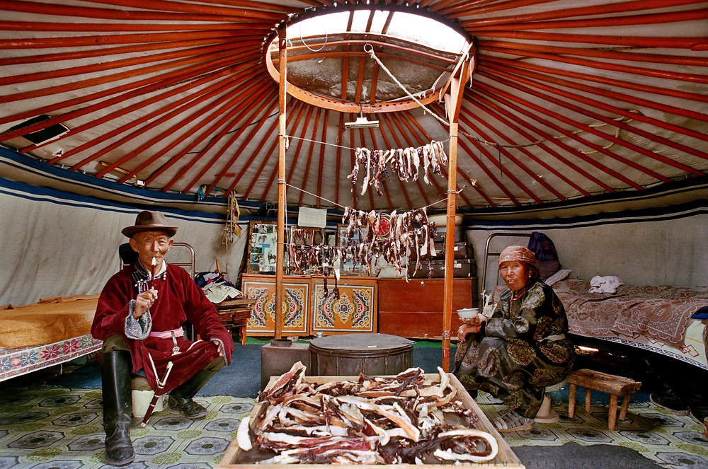 Inside Jolon's yurt, the mutton meat is dried in summer in order to face the long winter months. Every yurt throughtout Mongolia is organized the same way - beds, saddle, cupboard, pictures, stove etc are always at the same location.