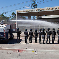Riot police in front of the National University of Honduras battle with students protesting on the anniversary of the assassination of Berta Cáceres.