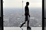 """Zac Vawter, fitted with an experimental """"bionic"""" leg, poses for a portrait on the Ledge at the Willis Tower, Thursday, Oct. 25, 2012 in Chicago. Vawter is training for the world's tallest stair-climbing event where he'll attempt to climb 103 flights to the top of theWillis Tower using the new prosthesis.  (AP)"""