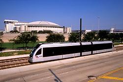 Houston Metro light rail passes by Reliant Stadium and the Astrodome