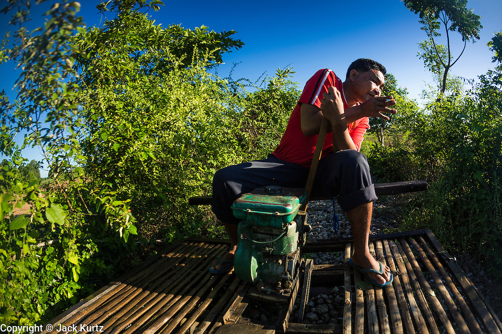 29 JUNE 2013 - BATTAMBANG, CAMBODIA:  A bamboo train driver ducks as low hanging weeds sweep over his train on the tracks near O Sra Lav, a small village southeast of Battambang. The bamboo train, called a norry (nori) in Khmer is a 3m-long wood frame, covered lengthwise with slats made of ultra-light bamboo, that rests on two barbell-like bogies, the aft one connected by fan belts to a 6HP gasoline engine. The train runs on tracks originally laid by the French when Cambodia was a French colony. Years of war and neglect have made the tracks unsafe for regular trains.  Cambodians put 10 or 15 people on each one or up to three tonnes of rice and supplies. They cruise at about 15km/h. The Bamboo Train is very popular with tourists and now most of the trains around Battambang will only take tourists, who will pay a lot more than Cambodians can, to ride the train.       PHOTO BY JACK KURTZ