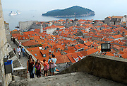 Elevated view of Dubrovnik old town and harbour, with people climbing Minceta Tower in foreground, and Lokrum Island in background. Dubrovnik, Croatia