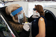 Registered nurse Denise Kuntz, left, administers a dose of the Moderna COVID-19 vaccine to Lisa Johnson, right, of Easton, as Lehigh Valley Health Network holds a COVID-19 mass vaccination clinic Mar. 20, 2021, at Pocono Raceway in Long Pond, Pennsylvania. Administrators were expected to vaccinate 3,000 people in the state of Pennsylvania's Phase 1A with the Moderna vaccine.