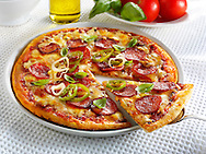 Pizza topped with Pepperoni, cheese, chilli & basil with a slice out photo. Funky Stock pizzas photos