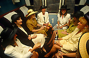 A group of attractive young ladies sit together in a train compartment. They are all on their way from London's Waterloo mainline station to Royal Ascot in Berkshire for Ladies Day during the Royal Ascot racing week. Wearing their best clobber and obligatory headwear for the posh event, the seated females are dressed in summer skirts and tops, in readiness for a warm day at the races. Sharing a joke and with plastic glasses filled with champagne from a bottle that one has been serving from, the 7 women are in good spirits in their private first class compartment that has a number 1 on the outside door. Royal Ascot is held every June and is one of the main dates on the sporting calendar and social season.
